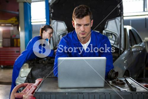 Attentive mechanic working on laptop