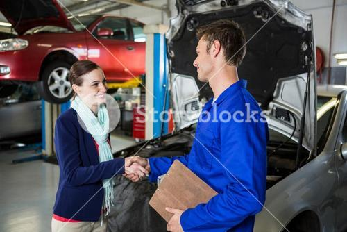 Satisfied customer shaking hands with mechanic