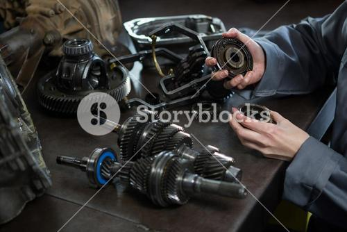 Female mechanic holding spare parts of car