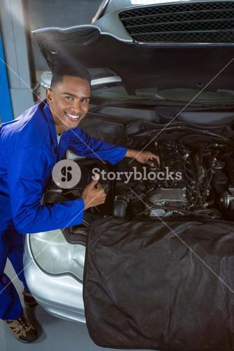 Mechanic showing thumbs up while repairing car