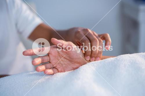 Physiotherapist giving hand massage to a woman