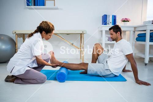 Physiotherapist doing leg therapy to a man using foam roll
