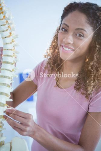 Portrait of woman holding spine model