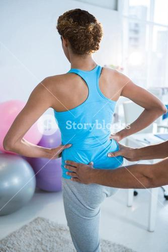 Physiotherapist examining womans back