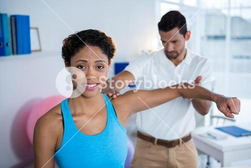 Physiotherapist examining womans shoulder