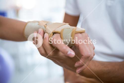 Physiotherapist examining hand of a female patient