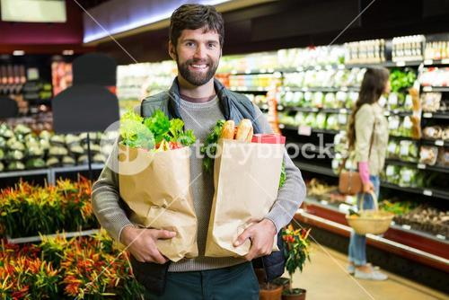 Portrait of smiling man holding a grocery bag in organic section