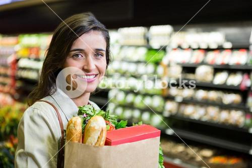 Portrait of smiling woman holding a grocery bag in organic section