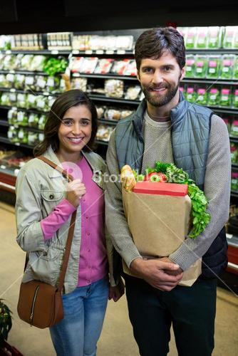 Couple shopping for vegetables in organic section of supermarket
