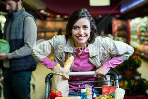 Portrait of smiling woman holding trolley in organic section