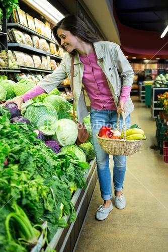 Woman buying vegetables in organic shop