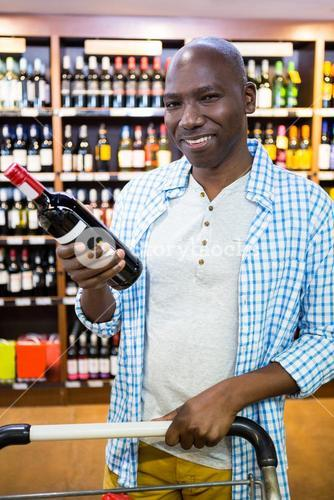 Portrait of man looking at wine bottle in grocery section