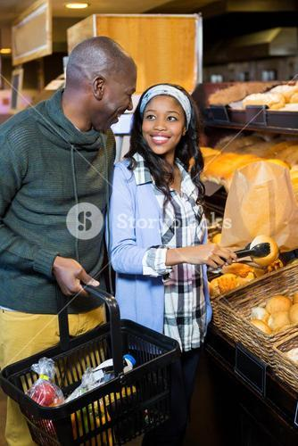 Smiling couple purchasing bread