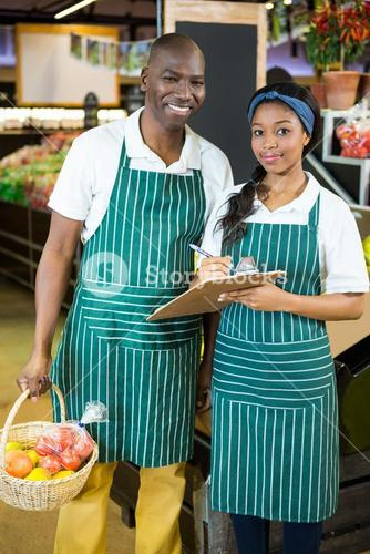 Staffs members maintain records on clipboard in supermarket