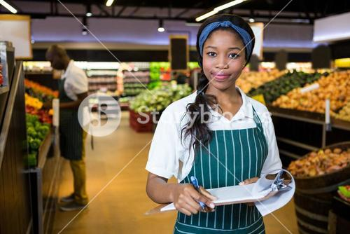 Female staff writing on notepad in super market