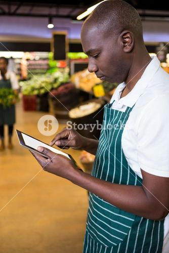 Male staff using digital tablet in organic section