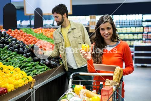 Happy couple selecting vegetables in organic section