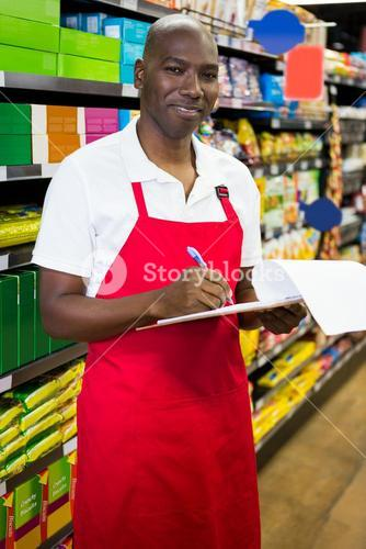 Smiling male staff writing on notepad in super market