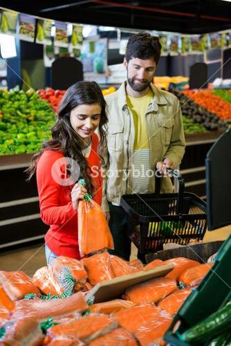 Couple buying vegetables in organic shop
