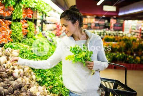 Smiling woman buying vegetables in organic shop