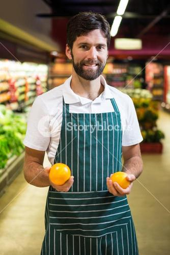 Smiling male staff holding fruit in organic section of supermarket