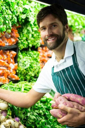 Male staff arranging vegetables in organic section