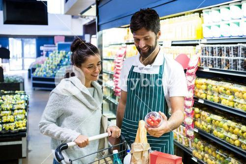 Smiling male staff assisting a woman with grocery shopping