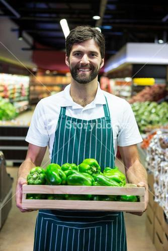 Smiling male staff holding a crate of green bell pepper at supermarket