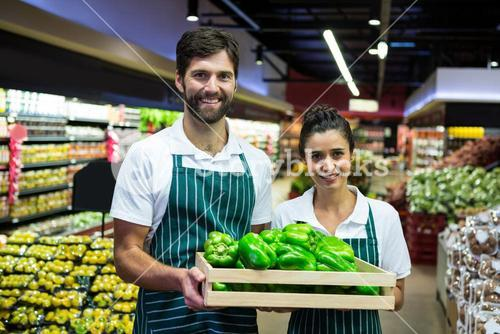 Smiling staff holding a crate of green bell pepper at supermarket