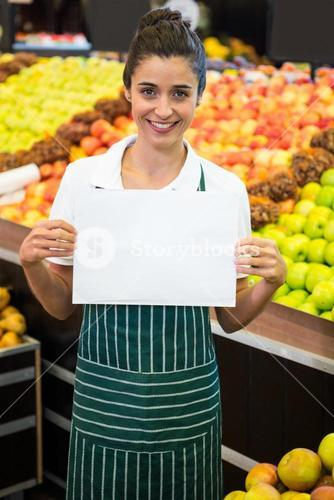 Smiling female staff holding a blank sheet at supermarket