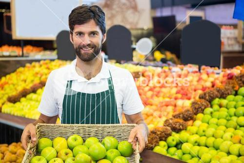 Smiling male staff holding a basket of green apple at supermarket