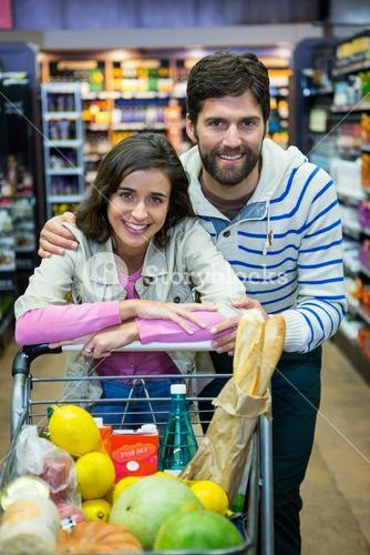 Happy couple leaning on trolley at supermarket