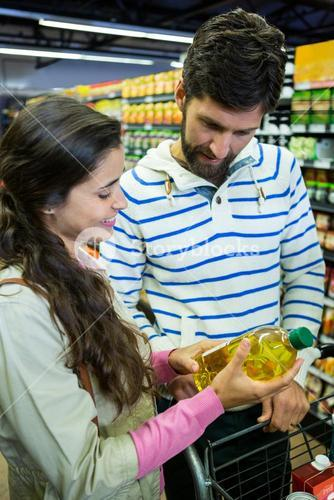 Couple buying oil bottle in grocery section