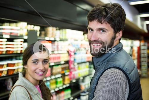 Portrait smiling couple in grocery section