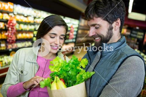 Couple holding grocery bag