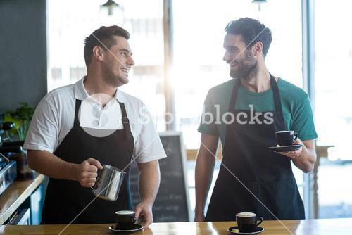 Smiling waiter interacting while making cup of coffee at counter
