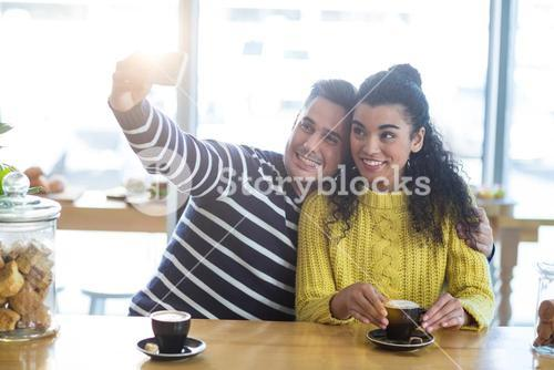 Young couple taking selfie in cafeteria