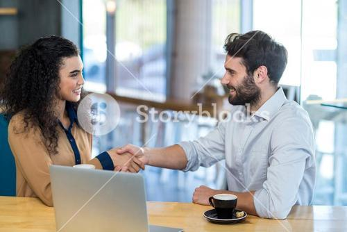 Couple shaking hands in café