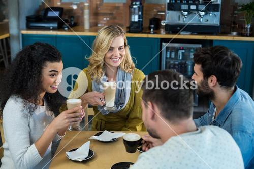 Smiling friends having a cup of coffee and cold coffee in café