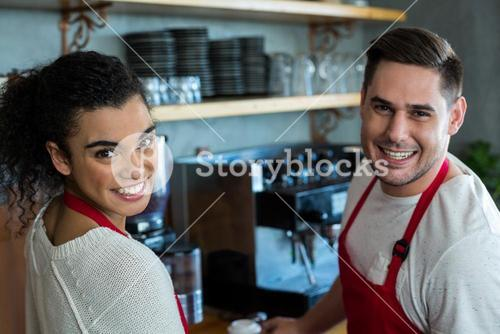 Smiling waitress and waiter in cafe