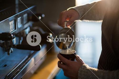 Waiter making cup of coffee at counter in cafe