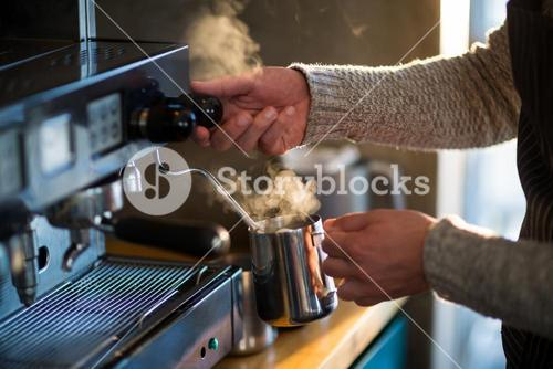 Waiter making cup of coffee at counter in kitchen