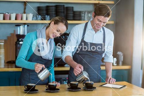Waiter and waitress making cup of coffee at counter in cafe