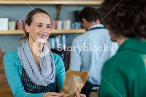 Waitress giving parcel to customer at counter