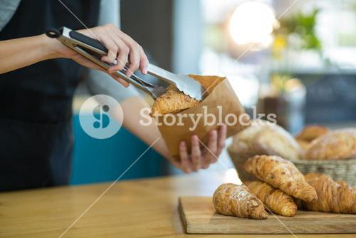Waitress packing croissants in paper bag at café