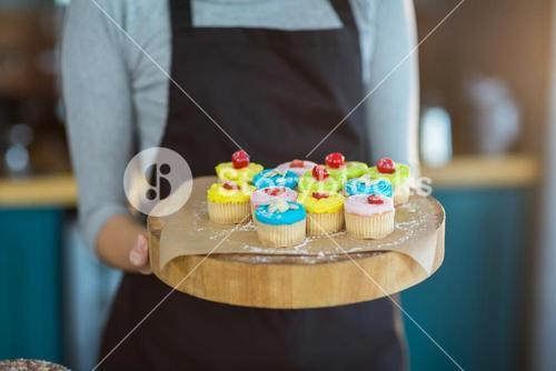 Waitress holding cup cake on tray in café