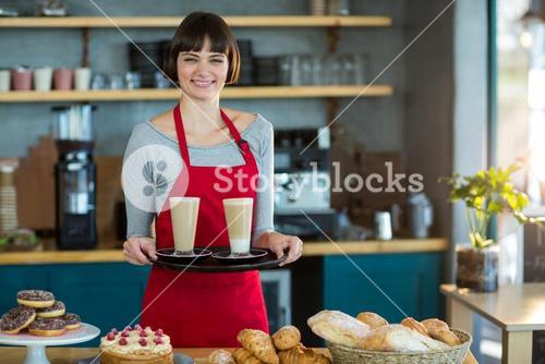 Portrait of waitress holding cup of cold coffee
