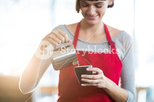 Waitress making cup of coffee at counter in cafe