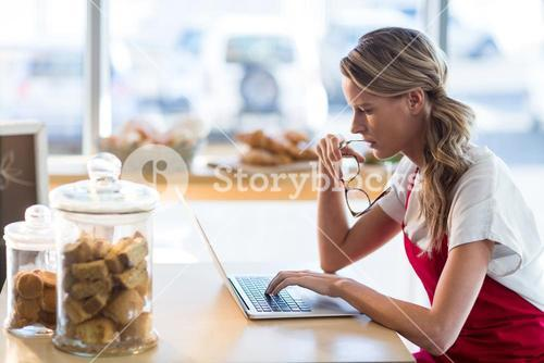 Waitress sitting at table and using laptop