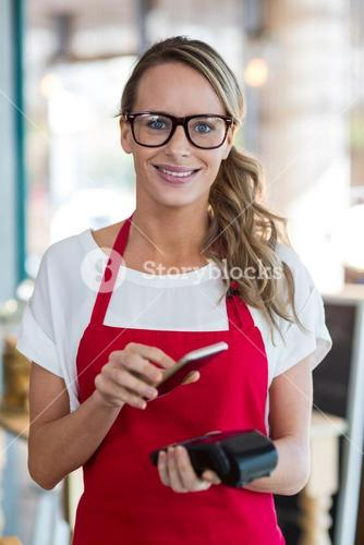 Woman scanning mobile phone with NFC technology